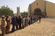보코하람의 공격으로 난민이 된 여성들이 성 테레사 성당에서 음식을 받기 위해 줄을 서 있다.